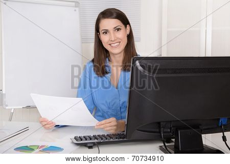 Successful Young Smiling Business Woman Sitting In Her Office.