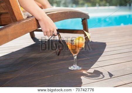 Close up of tropical juice on wood paneled floor by swimming pool