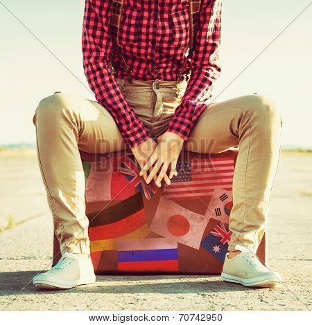 Woman Sits On Suitcase With Stamps Flags