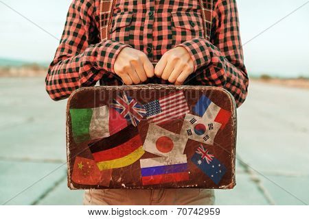 Woman Holds Small Suitcase With Stamps Flags