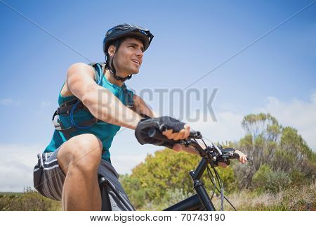 Low angle view of an athletic young man mountain biking