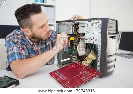 Computer engineer working on broken console with screwdriver in his office