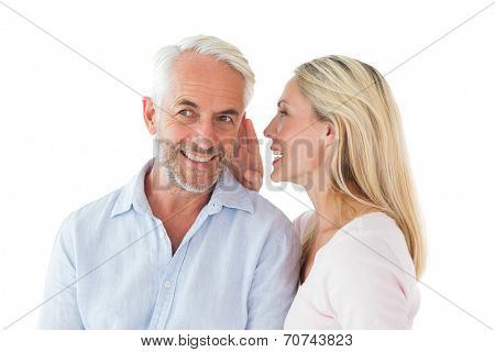 Woman whispering a secret to husband on white background