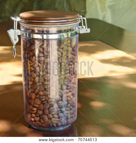 Coffee Beans In Transparent Glass Container On Wooden Table.
