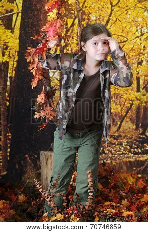 A pretty elementary girl in an autumn woods shielding her eyes as she peers into the distance.