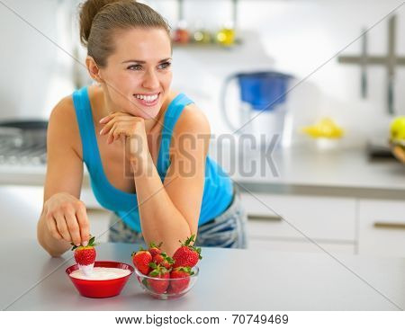 Happy Young Woman Eating Strawberry With Yogurt