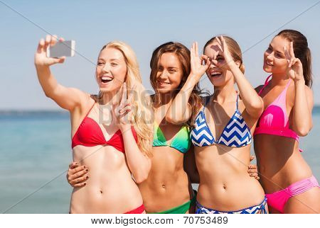 summer vacation, holidays, travel, technology and people concept- group of smiling young women on beach making selfie with smartphone over blue sky background