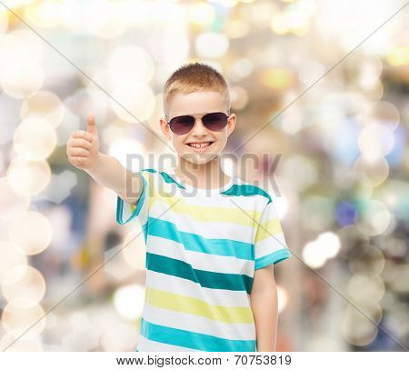 happiness, summer, gesture, childhood and people concept - smiling cute little boy in sunglasses over sparkling background showing thumbs up