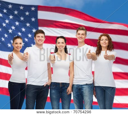 advertising, friendship, patriotism and people concept - group of smiling teenagers in white blank t-shirts showing thumbs up over american flag background