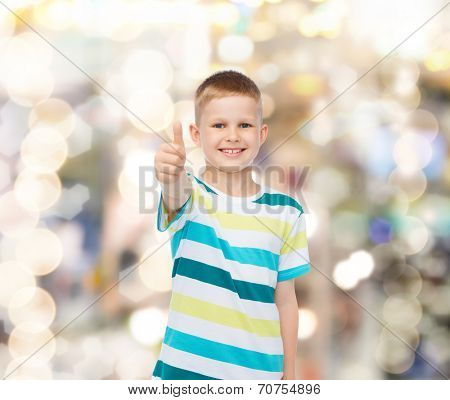 happiness, childhood, holidays, gesture and people concept - smiling little boy showing thumbs up over sparkling background