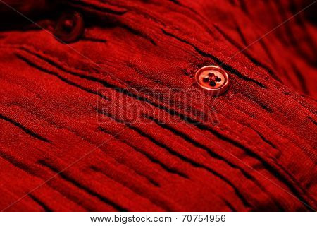 Detailed closeup macro of red button on red shirt