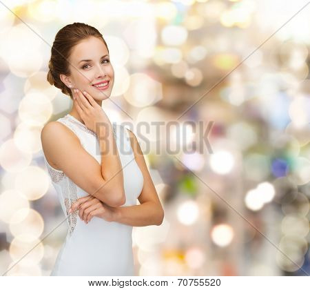 holidays, celebration, wedding and people concept - smiling woman in white dress wearing diamond ring over golden lights background
