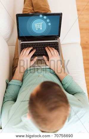 technology, leisure, advertisement and lifestyle concept - close up of man working with laptop computer displaying shopping trolley icon on screen and sitting on sofa at home