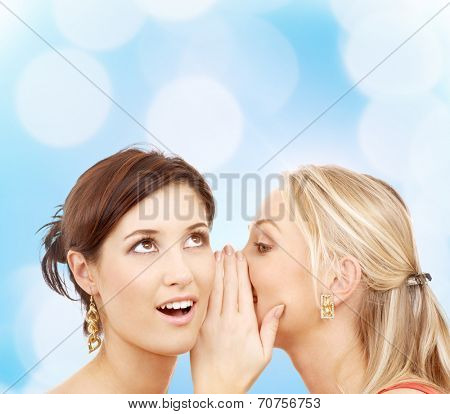 friendship, happiness and people concept - two smiling young women whispering gossip