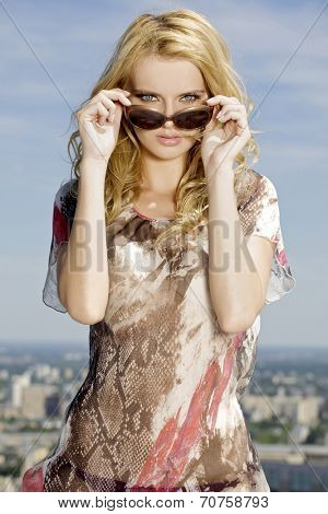 portrait of beautiful sexy and attractive young adult  blonde girl in sunglasses on background blue sky