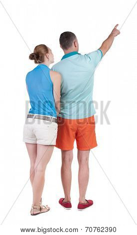 young couple in short pointing at wal Back view  (woman and man). Rear view people collection.  backside view of person.  Isolated over white background.