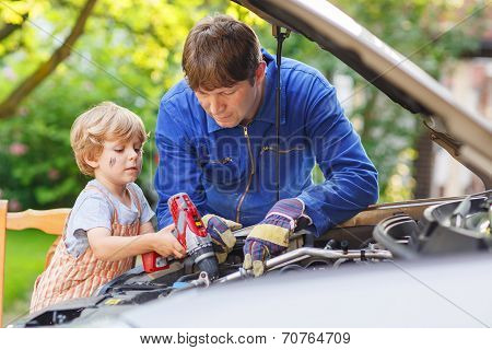 Young Father Teaching His Little Son To Repair Motor Oil In Family Car
