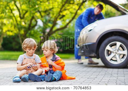 Two Little Sibling Boys In Orange Safety Vest During Their Father Repairing Family Car