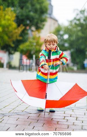 Happy Little Boy With Yellow Umbrella And Colorful Jacket Outdoors At Rainy Day