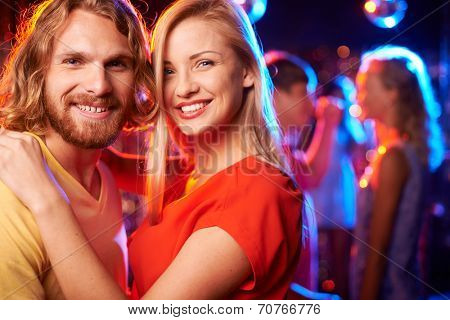 Happy young dates looking at camera at party in the night club