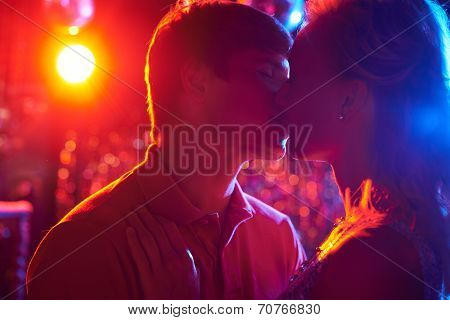 Amorous couple kissing while dancing in the night club