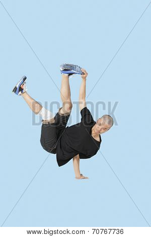 Break dancer performing handstand over blue background