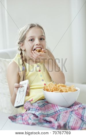 Girl watching TV as she stuffs her mouth with wheel shape snack pellets