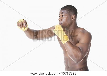 African American male boxer kickboxing over gray background