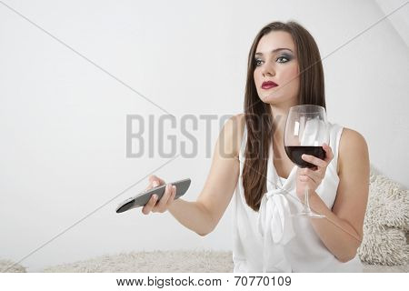 Young woman holding wineglass while changing channels with remote control