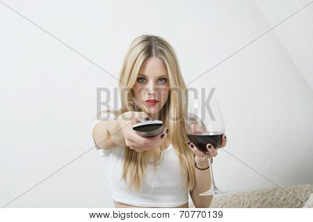 Portrait of a young woman holding wine glass while using remote control