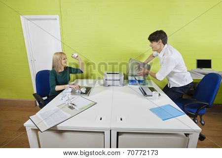Young businesswoman throwing paper ball at male colleague holding waste bin
