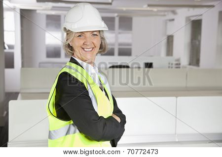 Portrait of smiling senior woman in reflector vest and hard hat at office