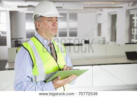 Middle-aged man in reflector vest and hard hat with clipboard at office