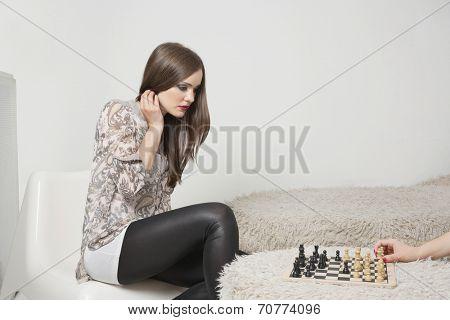 Beautiful young woman playing chess