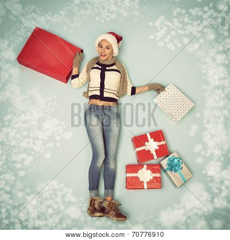 Christmas girl with gift and shopping bags in snowflakes