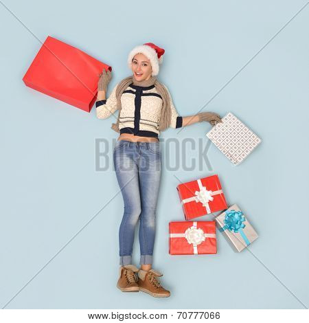 Christmas girl with gift and shopping bags in santa's hat over blue background