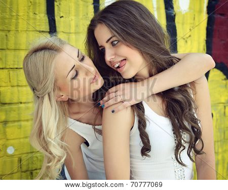 Two happy beautiful teen girls having fun outdoor against colored wall, image toned.