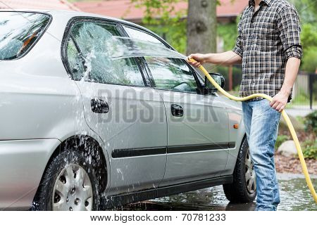 Man Rinsing Foam From Car