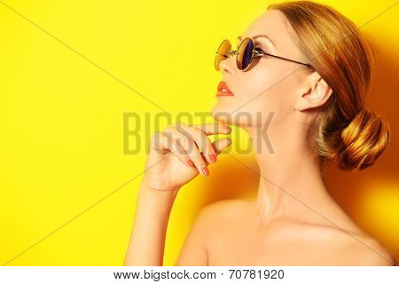 Beautiful elegant lady over bright yellow background. Beauty, fashion concept. Optics.