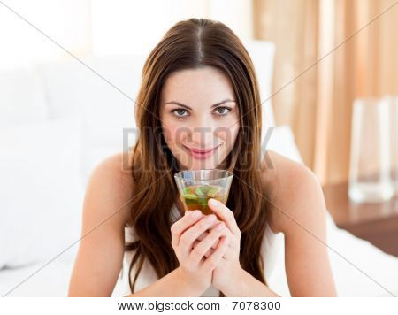 Portrait Of A Young Woman Drinking Tea Sitting On Bed