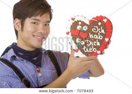 Mand Holding Oktoberfest Gingerbread Heart And Give Kiss