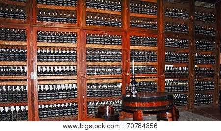 MADEIRA, PORTUGAL - OCTOBER 8, 2011: Wooden shelves with bottles of wine. Storage space for expensive aged wines - Madeira. Round table with  bottle, which is inserted the candle