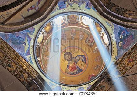 JERUSALEM, ISRAEL - MARCH 9, 2012: Gorgeous round arch ceiling lit by two bright rays of the sun. On the ceiling in the Hall of the Holy Sepulchre image of Christ the Savior
