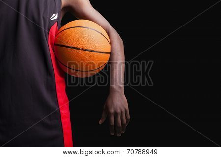 Basketball player standing with a basket ball on black background
