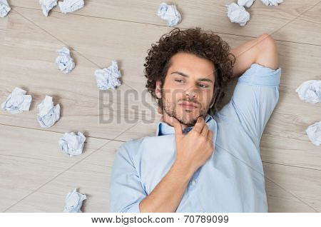 Contemplated Young Man Lying On Floor Surrounded With Crumpled Paper