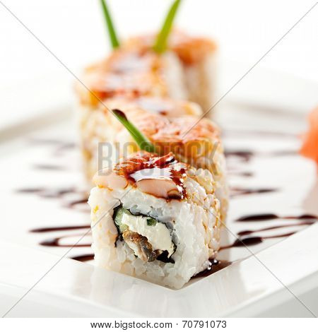 Japanese Cuisine - Sushi Roll with Cucumber, Cream Cheese and Smoked Eel inside. Topped with Shrimp. Garnished with Unagi Sauce