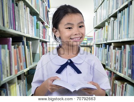 Portrait Of Cute Schoolgirl Smiling While Reading