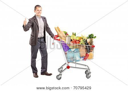 Satisfied man with a cart full of groceries isolated on white background