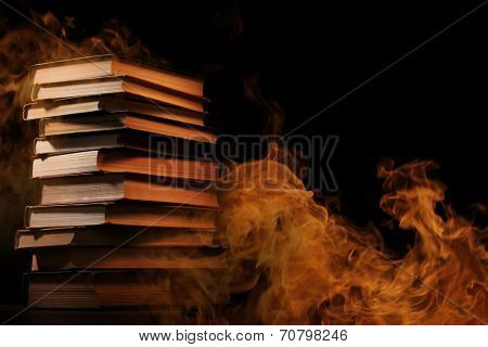 Pile of hardcover books surrounded with swirling tendrils smoke or vapor in a darkened vintage style room conceptual of magic, fire, spirituality or alchemy