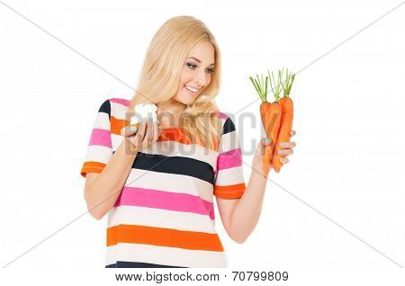 Beautiful young woman choosing between fresh carrot and cake